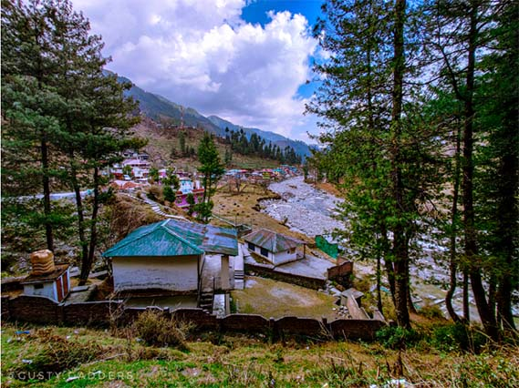 small colorful huts in valley with Uhl river beneath and mountains in the backdrop
