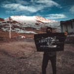 A Travel Photographer bearing a flag in Spiti